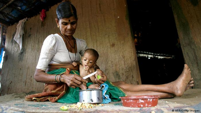 (FILES) Int his photograph taken on July 24, 2007, Indian tribal woman Hira Bai takes care of her grandchild Rohit in their mud and bamboo reinforced hut in Devipada, a tribal settlement in the remote forestland of Aarey Milk Colony on the outskirts of Mumbai. (Photo: PAL PILLAI/AFP/Getty Images)