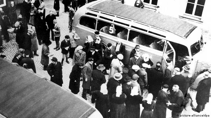 Fotografija prikazuje brojne žrtve nacističke eutanazije. Ljudi stoje ispred autobusa kod bolnice za mentalna oboljenja i čekaju na prijevoz do mjesta gdje će biti ubijeni.