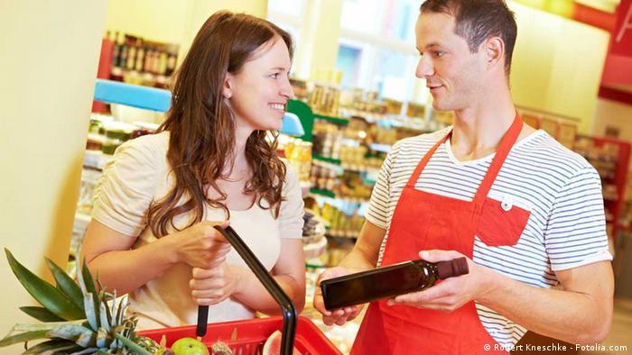 In einem Supermarkt zeigt ein freundlicher Verkäufer einer lächelnden Kundin eine Flasche Öl