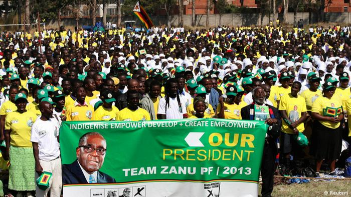 Supporters of Zimbabwean President Robert Mugabe holding up a banner with his picture.