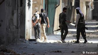 Free Syrian Army fighters hold their weapons as they walk along a damaged street near the frontline where clashes with forces loyal to Syria's President Bashar al-Assad are taking place in Beit Hajira near Damascus, July 7, 2013. Picture taken July 7, 2013. REUTERS/Ward Al-Keswani (SYRIA - Tags: CONFLICT)