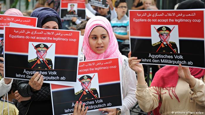 Women in headscarves holding red and black banners saying The Egyptian people reject the military putsch Foto: Ole Spata/dpa