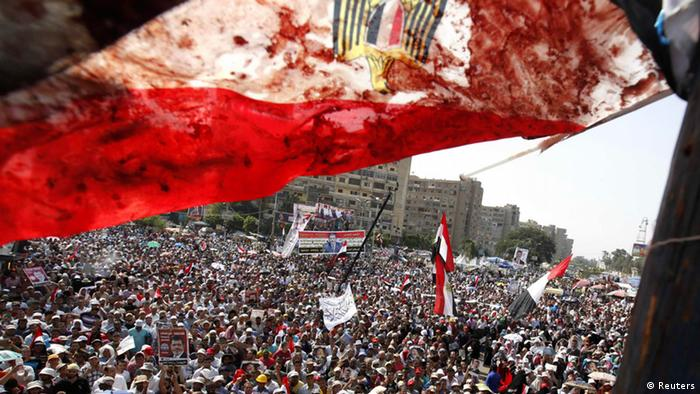 An Egyptian flag stained with blood flutters over members of the Muslim Brotherhood and supporters of deposed Egyptian President Mohamed Mursi as they shout slogans during a protest outside Raba El-Adwyia mosque in Cairo July 8, 2013, following clashes in front of the Republican Guard headquarters. At least 51 people were killed on Monday when demonstrators enraged by the military overthrow of Egypt's elected Islamist president said the army opened fire during morning prayers outside the Cairo barracks where Mursi is believed to be held. REUTERS/Mohamed Abd El Ghany (EGYPT - Tags: POLITICS CIVIL UNREST TPX IMAGES OF THE DAY)
