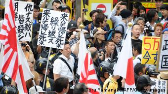 Carrying Japanese national flags and navy flags, members of a nationalist group march on the street of Korean Town in Tokyo during a demonstration denouncing South Korean people on June 16, 2013. (Foto: AFP)