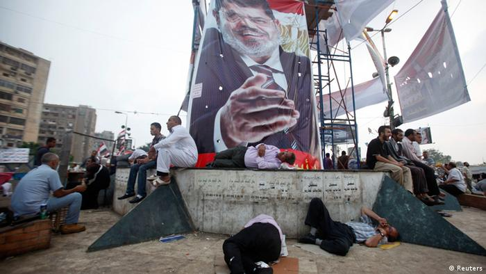Supporters of deposed Egyptian President Mohamed Mursi (pictured in poster) sleep at the Rabaa Adawiya square where they are camping in Cairo July 9, 2013. Egypt's interim head of state has set a speedy timetable for elections to drag the Arab world's biggest country from crisis, after the military ouster of Mursi last week sparked a wave of bloody protests. REUTERS/Khaled Abdullah