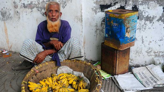An elderly man sells bananas