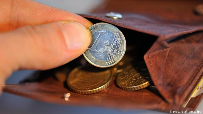 A one euro coin is removed by hand from a wallet (Photo: Andreas Gebert/dpa)