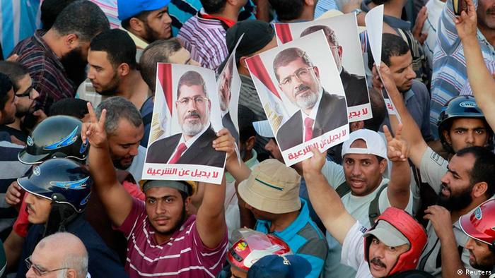 Supporters of deposed Egyptian President Mohamed Mursi hold posters during a protest outside Rabaa Adawiya mosque in Cairo July 9, 2013. Egypt's interim President Adli Mansour on Tuesday named liberal economist and former finance minister Hazem el-Beblawi as prime minister in a transitional government, as the authorities sought to steer the country to new parliamentary and presidential elections. The posters read, No substitute for the legitimacy. REUTERS/Louafi Larbi (EGYPT - Tags: POLITICS CIVIL UNREST)