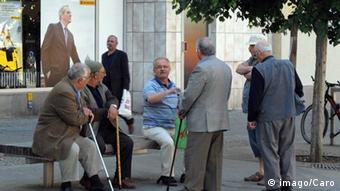 A group of elderly men sit and stand near a bench, talking Copyright: imago/Caro Berlin, Deutschland -