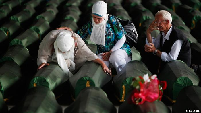 Bosnians cry near coffin of their relative, one of 409 newly identified victims of the 1995 Srebrenica massacre, in Memorial Center Potocari near Srebrenica July 10, 2013. The bodies of the recently identified victims will be transported to the memorial centre in Potocari where they will be buried on July 11 marking the 18th anniversary of the massacre in which Bosnian Serb forces commanded by Ratko Mladic killed up to 8,000 Muslim men and boys and buried them in mass graves. REUTERS/Dado Ruvic (BOSNIA AND HERZEGOVINA - Tags: SOCIETY ANNIVERSARY CIVIL UNREST)