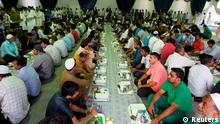 Labourers sit down before their first iftar, or breaking-fast, meal during the Muslim fasting month of Ramadan at an iftar tent in Riyadh July 10, 2013. REUTERS/Faisal Al Nasser (SAUDI ARABIA - Tags: RELIGION FOOD SOCIETY)