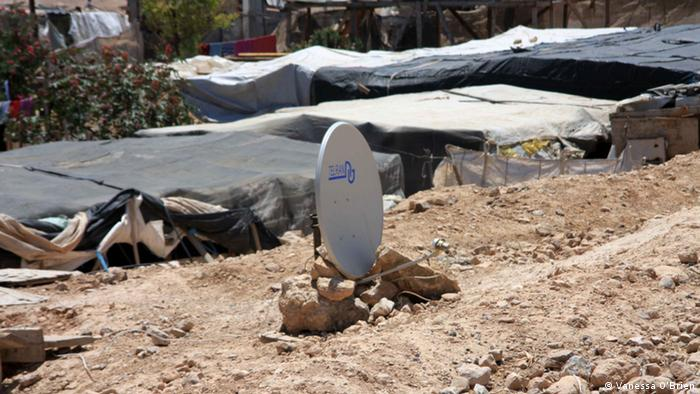 Lone satellite dish against backdrop of Bedouin camp