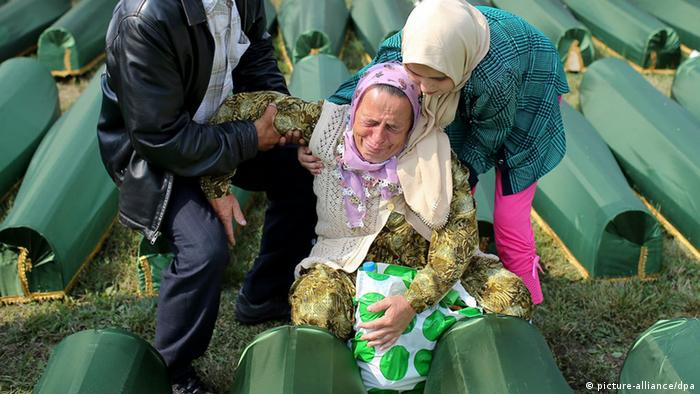 Bosnian women cry near the coffins of their relatives at the Potocari Memorial Center in Srebrenica, Bosnia and Herzegovina, 11 July 2013, during the burial of 409 newly-identified Bosnian Muslims as part of a memorial ceremony to mark the 18th anniversary of the Srebrenica massacre, considered the worst atrocity of Bosnia's 1992-95 war. More than 8,000 Muslim men and boys were executed in the 1995 killing spree after Bosnian Serb forces overran the town. EPA/VALDRIN XHEMAJ +++(c) dpa - Bildfunk+++