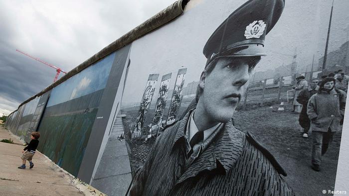 Ein Panoramabild auf der Berliner Mauer zeigt ein historisches Foto eines Wächters der Berliner Mauer. (c) REUTERS/Thomas Peter