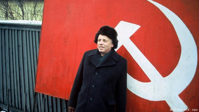 Sakharov in front of the hammer and sickle of a Soviet flag