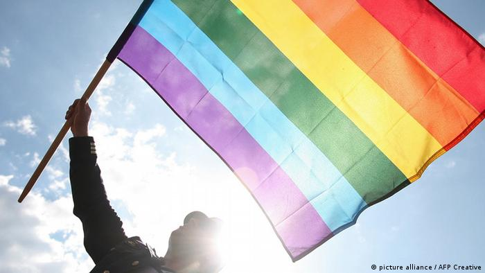 a man waves the rainbow flag