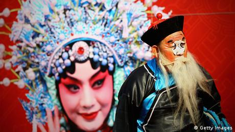 Bearded man stands in front of a large picture of a Beijing opera singer (Getty Images)