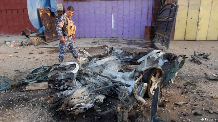 An Iraqi policeman inspects the site of a car bomb attack in Kirkuk, 250 km (155 miles) north of Baghdad, July 11, 2013. Two civilians were wounded in the car bomb attack, police said. REUTERS/Ako Rasheed