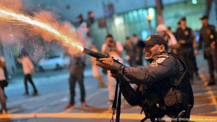 A riot police officer fires tear gas at violent demonstrators after clashes erupted following a march by Brazilian workers in Rio de Janeiro on July 11, 2013 in a day of industrial action called by major unions to press demands for better work conditions. Demonstrators on Thursday blocked roads and staged protest rallies across the country on the National Day of Struggles which was called by the country's five leading labour federations during last month's mass street protests to demand better public services and an end to endemic corruption. AFP PHOTO / CHRISTOPHE SIMON (Photo credit should read CHRISTOPHE SIMON/AFP/Getty Images)