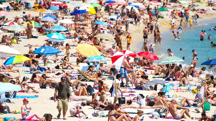 BARCELONA, SPAIN - AUGUST 04: People sunbathe at the La Mar Bella Beach on August 4, 2012 in Barcelona, Spain. Tourism is the largest contributor to the welfare of Spain's economy. Catalonia is the main destination for tourists, with 6.3 million visitors for the first half of the year, 12.3% more than in 2011. (Photo by David Ramos/Getty Images)