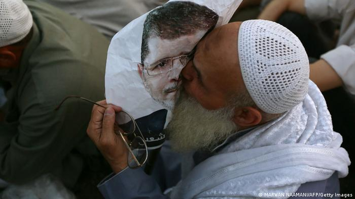An Egyptian man, supporter of the Muslim Brotherhood and Egypt's ousted president Mohamed Morsi kisses a poster of him as worshipers gather for a dusk payer outside Cairo's Rabaa al-Adawiya mosque on July 11, 2013, during the second day of Islam's holy fasting month of Ramadan. The people of Egypt are marking the Muslim fasting month of Ramadan amid soaring tensions following last week's ouster by the military of Islamist president Mohamed Morsi. AFP PHOTO/MARWAN NAAMANI (Photo credit should read MARWAN NAAMANI/AFP/Getty Images)