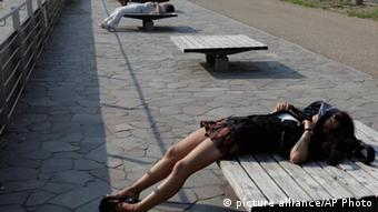 People sunbathe on benches at a park in Tokyo, (Photo: AP)