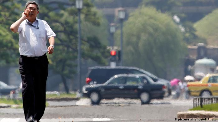 A man scratches his neck as he walks in the heat of the sun in Tokyo, Thursday, July 11, 2013.(Photo: AP)