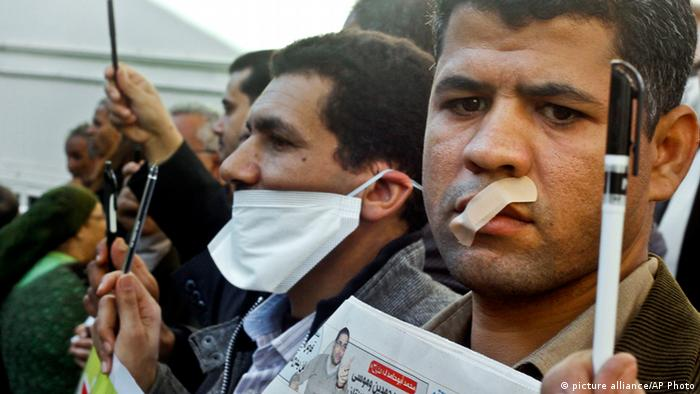 Egyptian journalists tape their mouths and raise their pens during a demonstration against the draft constitution in Cairo, Egypt, Sunday, Dec. 23, 2012. Egypt's opposition called Sunday for an investigation into allegations of vote fraud in the referendum on a deeply divisive Islamist-backed constitution after the Muslim Brotherhood, the main group backing the charter, claimed it passed with a 64 percent yes vote. Official results have not been released yet and are expected on Monday. (AP Photo/Amr Nabil)