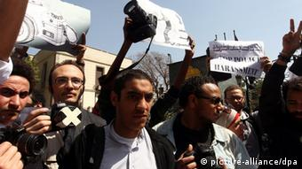 epa03631490 A handout photograph provided by the Egyptian Photojournalists Society (EPS) shows Egyptian photographers holding up their cameras as they protest the government's harsh policies against them in front of the Shura council, in Cairo, Egypt, 19 March 2013. Photographers gathered to protest recent attacks on colleagues by supporters of the ruling Muslim Brotherhood. Several journalists and cameramen said they had been attacked by baton-wielding supporters of the Muslim Brotherhood while covering a protest on 16 March outside the Islamist group's headquarters on the outskirts of Cairo. EPA/KHALED ELFIQI/EPS/HANDOUT HANDOUT EDITORIAL USE ONLY/NO SALES pixel