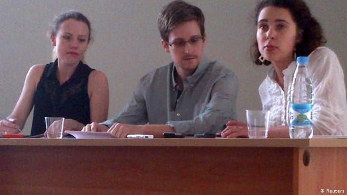 Former intelligence agency contractor Edward Snowden (C) and Sarah Harrison (L) of WikiLeaks speak to human rights representatives in Moscow's Sheremetyevo airport July 12, 2013. Snowden is seeking temporary asylum in Russia and plans to go to Latin America eventually, an organisation endorsed by anti-secrecy group Wikileaks said on Twitter on Friday. The person at right is unidentified. REUTERS/Human Rights Watch/Handout