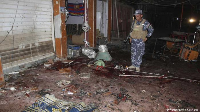 ATTENTION EDITORS - VISUAL COVERAGE OF SCENES OF INJURY OR DEATH An police officer inspects the site of a bomb attack at a coffee shop in Kirkuk, 250 km (155 miles) north of Baghdad, July 12, 2013. A bomb attack in a cafe in northern Iraq killed at least 31 people on Friday, police and medics said. The blast took place in the ethnically mixed city of Kirkuk, in a coffee shop where people had gathered after breaking their fast for the Muslim holy month of Ramadan. REUTERS/Ako Rasheed (IRAQ - Tags: CIVIL UNREST POLITICS) TEMPLATE OUT - eingestellt von gri