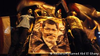 Members of the Muslim Brotherhood and supporters of deposed Egyptian President Mohamed Mursi hold a banner with his picture as they gather at the Rabaa Adawiya square, where they are camping, in Cairo July 12, 2013. Tens of thousands of Egyptians packed into squares and marched along streets in Cairo on Friday to protest against the military overthrow of Islamist President Mursi, and the United States called for the first time for him to be freed. REUTERS/Mohamed Abd El Ghany (EGYPT - Tags: POLITICS CIVIL UNREST TPX IMAGES OF THE DAY) - eingestellt von gri