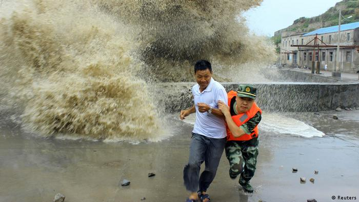 A frontier soldier helps a man move away from waves ahead of Typhoon Soulik in Wenzhou, Zhejiang province, July 13, 2013. China braced on Friday for the impact of Typhoon Soulik as the toll of dead and missing from torrential rain across a broad swathe of China climbed beyond 200. REUTERS/China Daily (CHINA - Tags: ENVIRONMENT TPX IMAGES OF THE DAY) CHINA OUT. NO COMMERCIAL OR EDITORIAL SALES IN CHINA