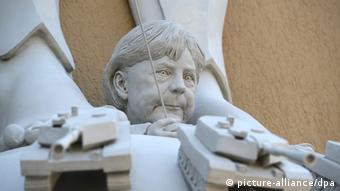 A close-up of the bottom of Peter Lenk's Kampf um Europa sculpture. At Europa's feet sits a head resembling German Chancellor Angela Merkel, and a hand with a remote control. Several tanks are in front of her. (Photo via Patrick Seeger/dpa