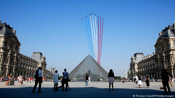 GettyImages 173430190 Nine alphajets from the French Air Force Patrouille de France releasing trails of red, white and blue smoke, colors of French national flag, fly over the Pyramid du Louvre during the Bastille Day parade, on July 14, 2013 in Paris. AFP PHOTO / THOMAS COEX (Photo credit should read THOMAS COEX/AFP/Getty Images)