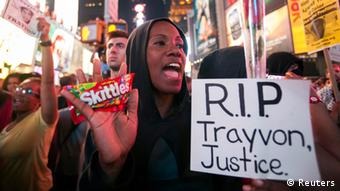 Protester Keisha Martin-Hall holds a bag of Skittles as she participates in a rally in response to the acquittal of George Zimmerman in the Trayvon Martin trial in Times Square in New York, July 14, 2013. U.S. President Barack Obama called for calm on Sunday after the acquittal of George Zimmerman in the shooting death of unarmed black teenager Trayvon Martin, as thousands of civil rights demonstrators turned out at rallies to condemn racial profiling. Zimmerman, cleared late on Saturday by a Florida jury of six women, still faces public outrage, a possible civil suit and demands for a federal investigation. REUTERS/Keith Bedford Les manifestations veulent que justice soit rendue à Trayvon Martin