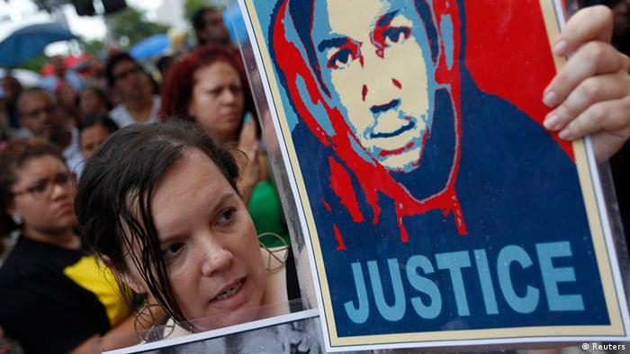 Annette Quintera from Miami holds an image of Trayvon Martin at a rally in Miami, Florida REUTERS/Andrew Innerarity (UNITED STATES - Tags: POLITICS CRIME LAW CIVIL UNREST)