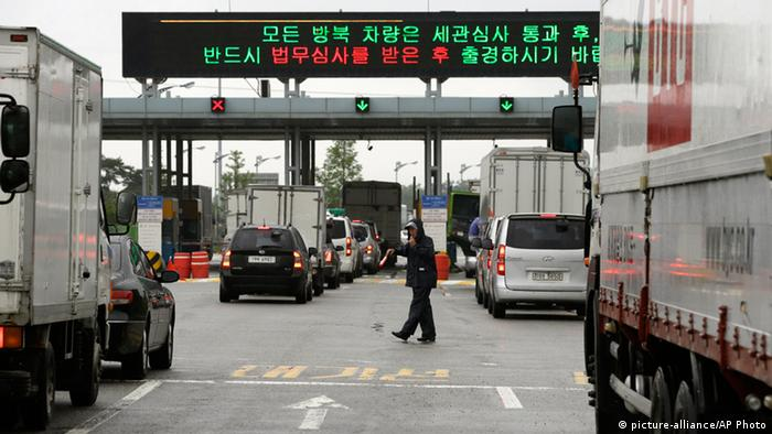 A security officer directs South Korean vehicles as they leave for South and North Korea's joint Kaesong Industrial Complex to bring back their finished goods and materials at the customs, immigration and quarantine office of the Inter-Korean Transit Office near the border village of Panmunjom, which has separated the two Koreas since the Korean War, in Paju, north of Seoul, South Korea, Monday, July 15, 2013. Talks aimed at restarting the factory park ended Wednesday with no breakthrough, but both sides agreed to meet again Monday to discuss restoring what was once a symbol of cooperation between the rivals. (AP Photo/Lee Jin-man)