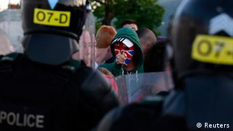 A Loyalist protester gestures to the police in the Woodvale Road area of North Belfast, July 14, 2013, on the third night of unrest after an Orange Parade was blocked from marching past the Nationalist Ardoyne area. (Photo:REUTERS/Cathal McNaughton)