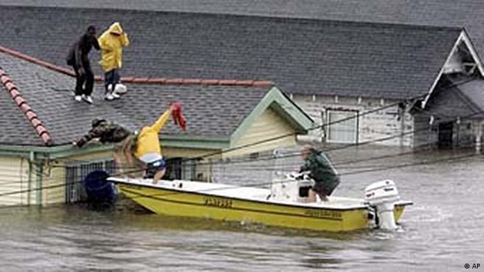 Duas pessoas em cima do telhado de uma casa são resgatadas por um barco. A água quase atinge o telhado das casas.