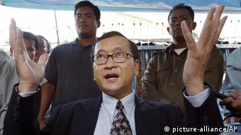 In this March 23, 2006 file photoay, , Cambodian opposition leader Sam Rainsy speaks to reporters outside the National Assembly building in Phnom Penh, Cambodia. Cambodian Prime Minister Hun Sen engineered a pardon for his most prominent rival Rainsy Friday, clearing the way for the self-exiled politician to return home and campaign in this month's general election. (Photo: AP)