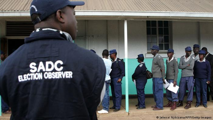 A SADC (Southern Africa Development Community) election observer looks on as Zimbabwe security forces queue to vote during the special voting day for registered members of the police and army in Harare on July 14, 2013. Zimbabwe security forces voted on July 14 in an early election marred by delays over a lack of ballot papers just over two weeks before crucial presidential polls. AFP PHOTO / Jekesai Njikizana (Photo credit should read JEKESAI NJIKIZANA/AFP/Getty Images)