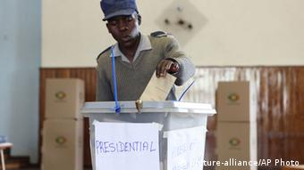 A Zimbabwean police officer casts his vote, at a polling station in Harare