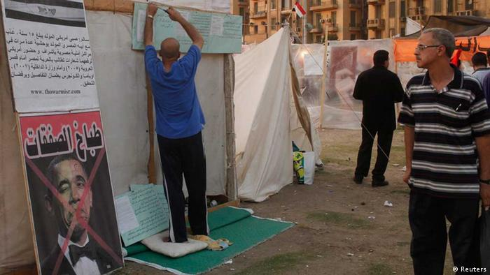 A protester hangs placards on his tent as a crossed-out picture of U.S. President Barack Obama is seen, in Tahrir square, Cairo, July 15, 2013. The first senior U.S. official to visit Egypt since the army toppled its elected president was snubbed by both Islamists and their opponents on Monday. Deputy Secretary of State William Burns arrived in a divided capital where both sides are furious at the United States, the superpower which supports Egypt with $1.5 billion in annual aid, mostly for the army that deposed Islamist President Mohamed Mursi two weeks ago. The text on the crossed-out picture of Obama reads, The guy who cooks up the deals. REUTERS/Asmaa Waguih (EGYPT - Tags: POLITICS CIVIL UNREST)