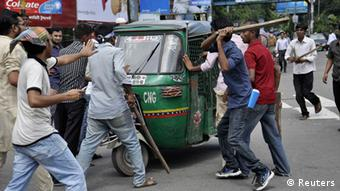 Protesters attempt to vandalize an auto rickshaw after hearing the verdict of the trial of Ghulam Azam (not pictured), the former head of Jamaat-e-Islami party as they demand his capital punishment in Dhaka July 15, 2013. Bangladesh's war crimes tribunal convicted and sentenced Azam, 91, to life imprisonment on Monday, in the fifth such conviction since January, as violence broke out between police and his supporters across the country. Azam was found guilty on charges of planning, conspiracy, incitement and complicity to commit genocide and crimes against humanity during a 1971 war to break away from Pakistan, lawyers and tribunal officials said. REUTERS/Stringer (BANGLADESH - Tags: POLITICS CRIME LAW)