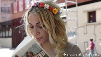 Leader of feminist organization Femen, Inna Shevchenko signs a copy of her book next to a giant poster by French street-art artist Combo showing Femen activists on a wall along Canal Saint-Martin to mark Bastille Day, in Paris, France on July 14, 2013. (Photo by Stephane Lemouton/ABACAPRESS. COM)