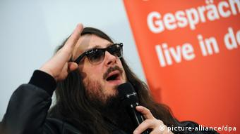 Jonathan Meese raising his arm in a Hitler salute