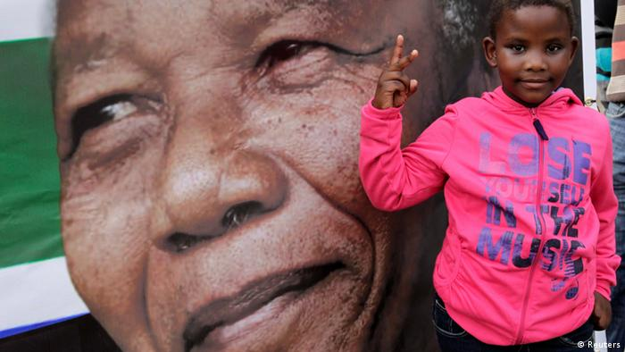 A girl gestures near a picture of ailing former South African President Nelson Mandela, outside the Medi-Clinic Heart Hospital where he is being treated in Pretoria July 6, 2013. REUTERS/Thomas Mukoya (SOUTH AFRICA)