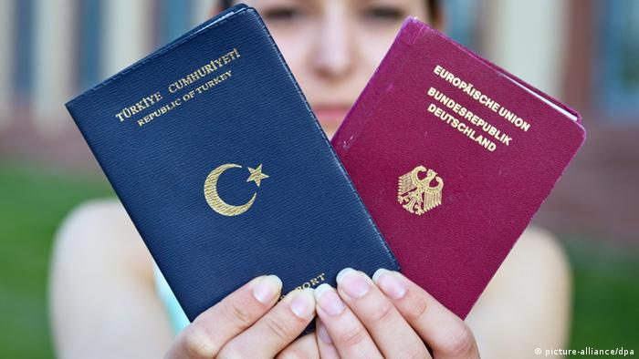 Student holds up German and Turkish passports (Foto: Daniel Bockwoldt/dpa)