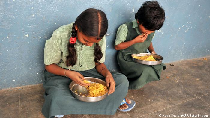 Indian children eat their mid-day meal at a Government High School in Hyderabad (Photo via Getty Images)